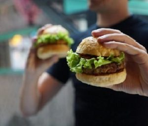 Guy Holding two burgers